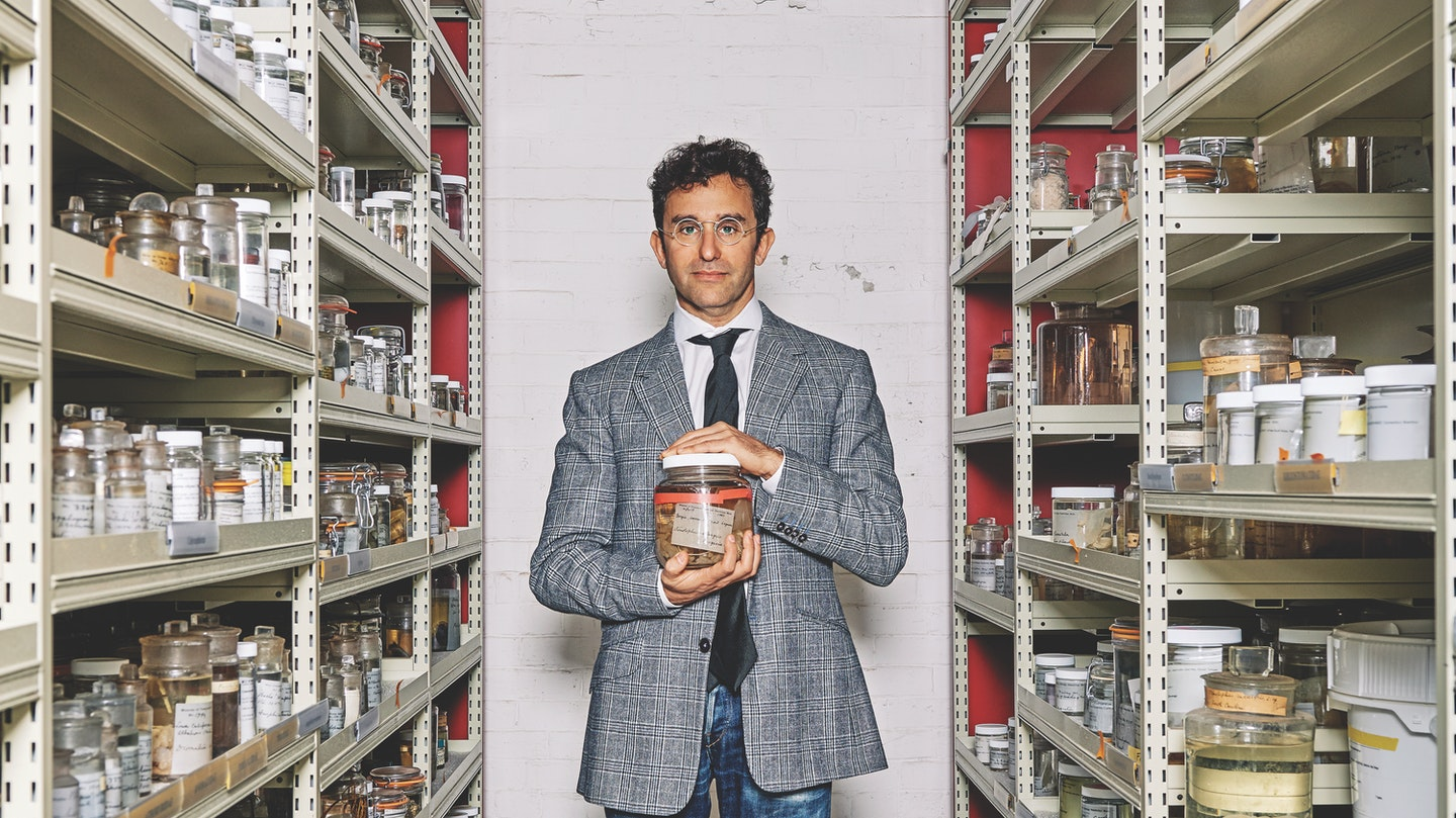 David Gruber standing in between shelves and holding a jar of some substance