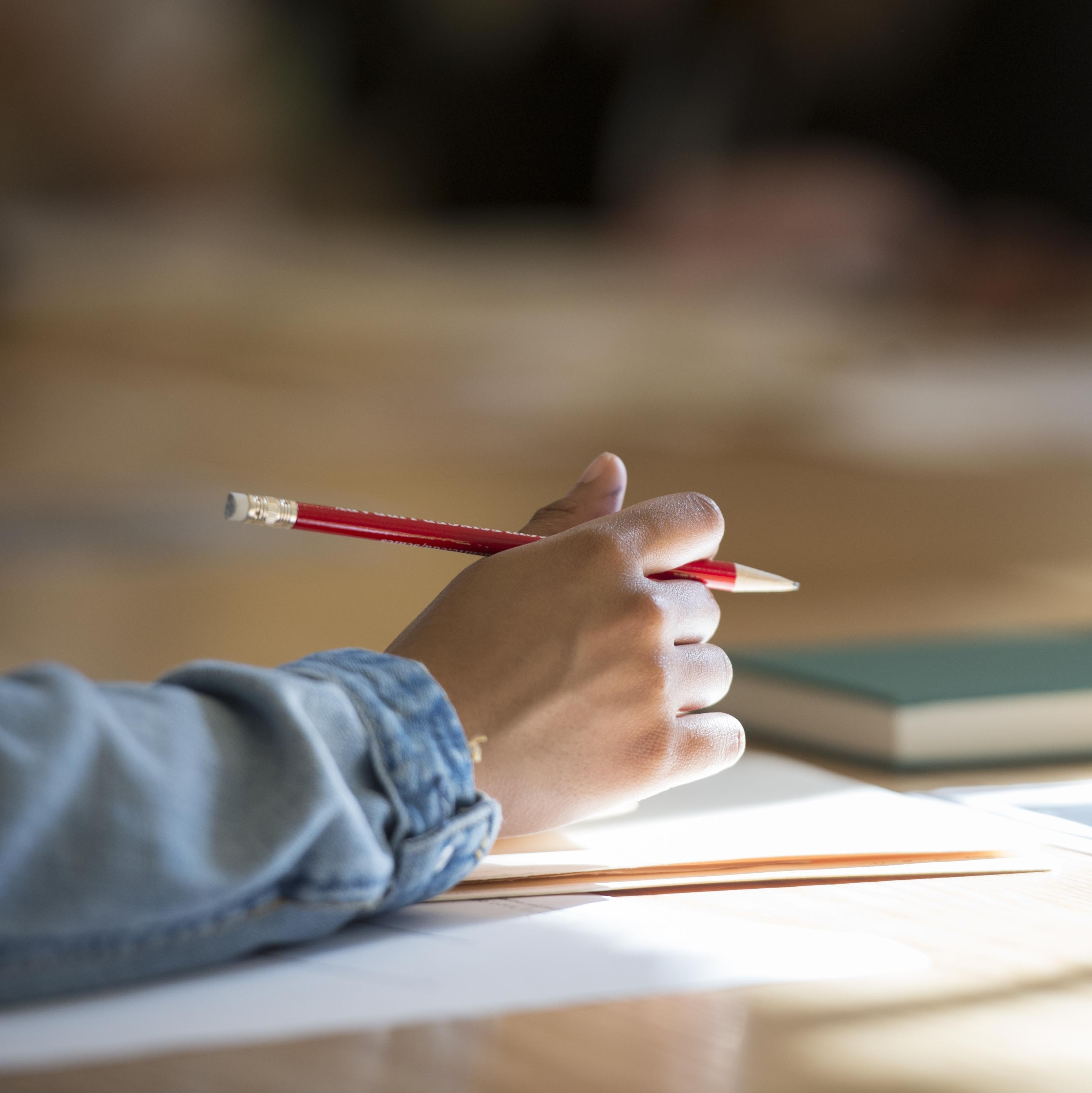Close-up of a researcher's hand holding a pencil with books and papers in the background.